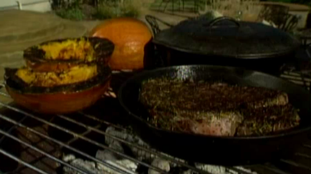 Grilled pumpkin, steak, soup and bread on fire pit