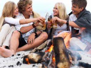 Young group of people sitting by bonfire at the beach drinking